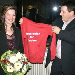 """Jürgen Horn überreicht Kathrin Plotke ein Jogging-Shirt mit der Aufschrift: """"Warmlaufen für Uedem""""."""